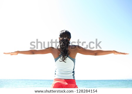 "Rear view of an ""african american"" woman stretching her arms to the sides while standing against a deep blue sky, exercising on a sunny day by the sea."