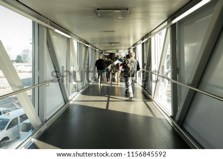 Rear view of an Airline Passengers in the airport bridge, Jet bridge where passengers connect with the plane.   airport terminal.