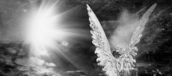 Rear view of an angel with wings in the rays of light. Antique statue. Black and white image.