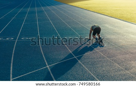 Rear view of an athlete ready to sprint on an all-weather running track. Runner using a starting block to start his run on race track. #749580166