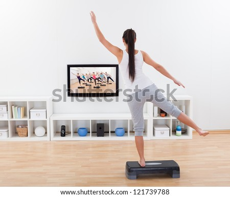Rear view of an athletic barefoot young woman doing home exercises while watching program on television