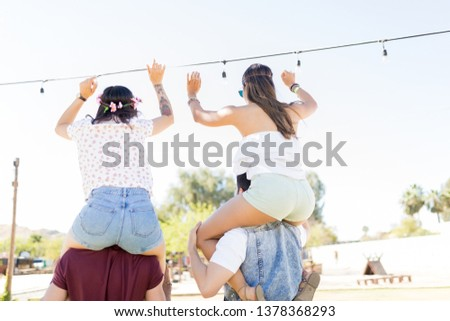 Rear view of an enthusiastic women with male friends during summer music festival