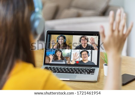 Rear View of Asian Business woman say hello with teamwork colleague in video conference when Coronavirus outbreak, Covid-19 pandemic, online meeting, Social distancing and new normal concept