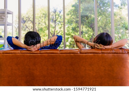 Rear view of asian couple relaxing on sofa in living room at home and looking green tree and green leaves background through the glass of room. Lifestyle and vacation relaxation concept.