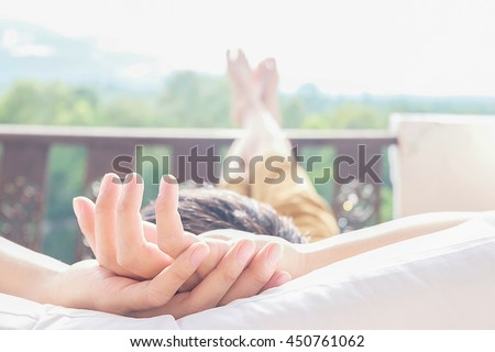 Rear view of asian man relaxing on a sofa and looking outside a green background view at home terrace. Relaxing concept. #450761062