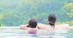 rear view of asian mother and daughter enjoy outdoor hot spring