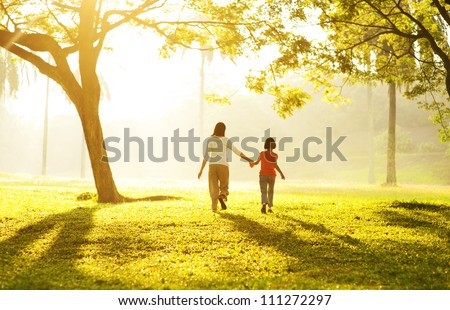 Rear view of Asian mother holding her daughter's hand running towards light #111272297
