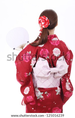 Rear view of asian woman in traditional clothes of kimono with paper fan - stock photo