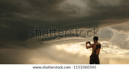 Rear view of athlete taking pictures of dramatic sky with his mobile phone. Fit man capturing cloudy sky pictures in his mobile phone while workout break.