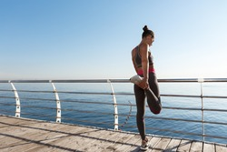 Rear view of attractive fitness woman stretching her legs before jogging, leaning on handrail along seaside promenade, training outdoors