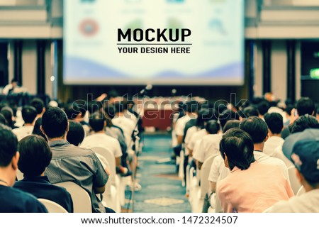 Rear view of Audience listening Speakers on the stage with presentation via projector in the conference hall or seminar meeting and workshop event, business and education about investment concept