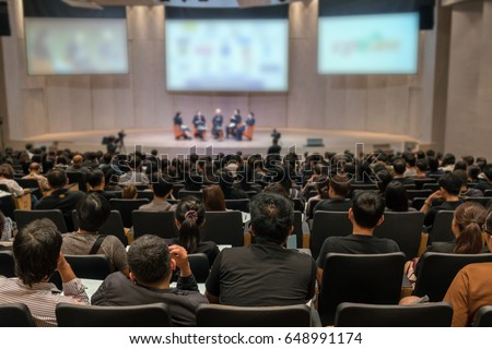 Rear view of Audience over the speakers on the stage in the conference hall or seminar meeting, business and education concept