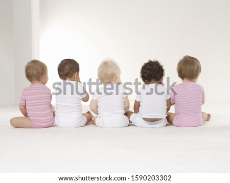 Rear view of babies sitting on floor