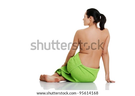 Rear view of beautiful nude caucasian woman with towel around her waist, isolated on white background
