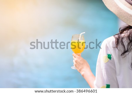 Rear view of beautiful woman in hat is holding orange juice glass at poolside in summer. #386496601