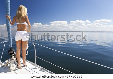 Rear view of beautiful young woman standing on the bow of a sail boat on a tranquil calm blue sea
