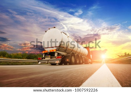 Rear view of big metal fuel tanker truck in motion shipping fuel on the countryside road against night sky with sunset