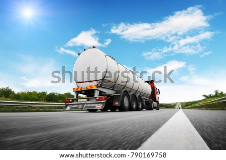 Rear view of big metal fuel tanker truck in motion shipping fuel on the countryside road against blue sky
