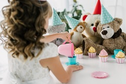 rear view of birthday kid having tea party with teddy bears in cones at table with cupcakes