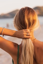 Rear view of blond woman arranging her hair. Warm sunset colors. Back view of pretty woman walking on the beach.