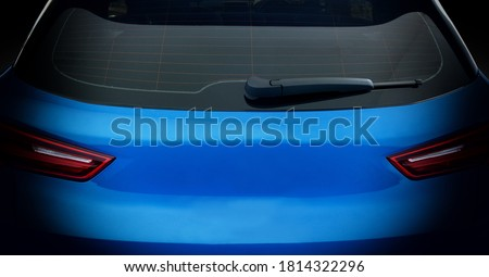 Rear view of blue car with rear wiper, defogger wires and rear lights on dark tone background. ストックフォト ©