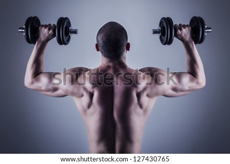 Rear view of bodybuilder training with dumbbells. Back muscles