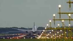 Rear view of Boeing of Unnited Airlines landing at Schiphol airport at sunset. Shot from the beginning of runway.