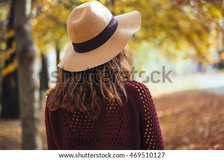 Rear view of brunette girl in autumn/fall park in brown hat, sweater and trousers. Back view of autumn portrait of woman outdoors with curly hair #469510127