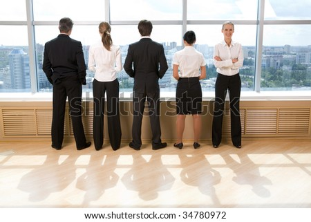 Rear view of business group standing in row and looking through window with their leader smiling at camera