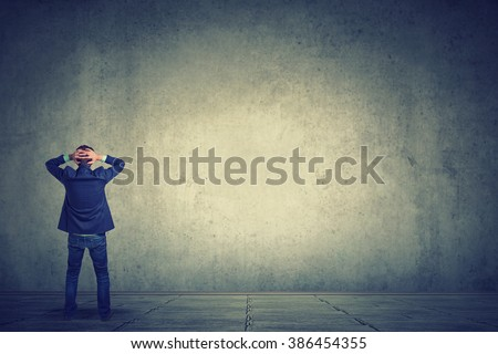 Rear view of business man standing in front of a wall hands on head wondering what to do next. Full length of businessman facing the wall