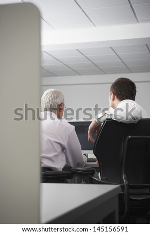 Rear view of business people using computer in office cubicle