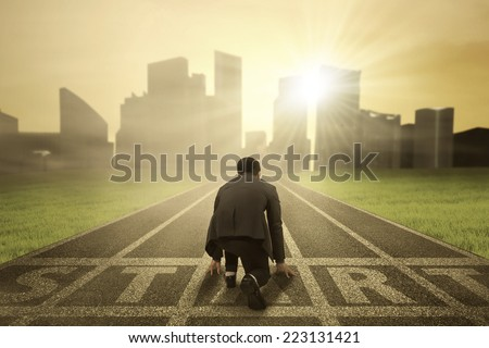 Shutterstock Rear view of business person in ready position on start line to compete