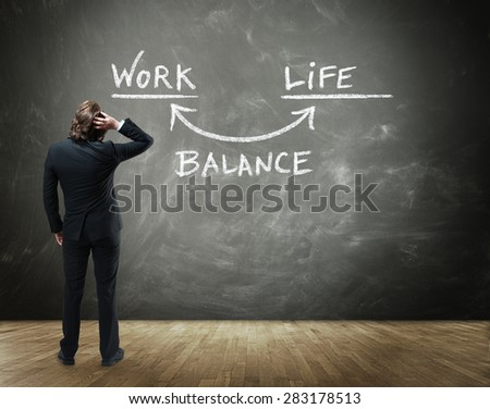 Rear View of Business Person Scratching Head in Confusion While Contemplating Illustration of Work Life Balance Drawn on Chalkboard in Business Balance Concept Image