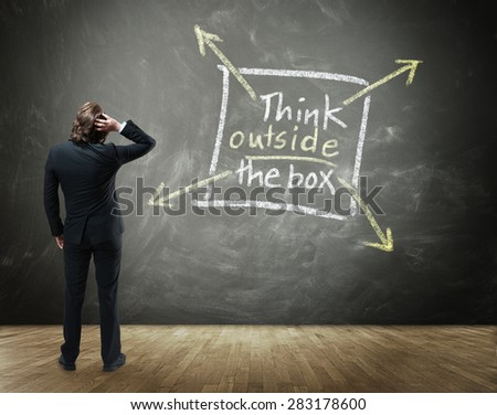 Rear View of Business Person Scratching Head with Hand in Confusion Standing in front of Chalkboard with Drawing Illustrating Creative Thinking - Think Outside the Box Concept