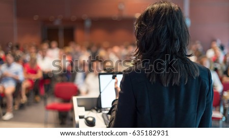 Rear view of business woman at lectern lecturing at Conference. Audience at the lecture hall. #635182931