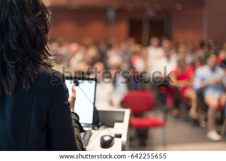 Rear view of business woman at lectern lecturing at Conference. Audience at the lecture hall.