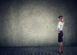 Rear view of business woman standing by the wall with hand on head wondering what to do next being challenged. Full length of businesswoman facing the obstacle