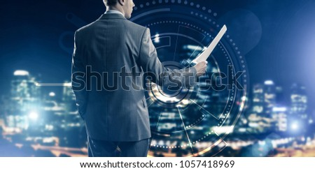 Rear view of businessman against virtual panel interface holding papers in hand #1057418969