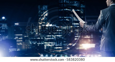 Rear view of businessman against virtual panel interface holding papers in hand #583820380