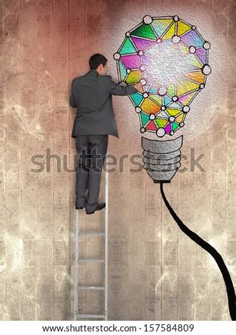 Rear view of businessman pointing at painted bulb on brown wall while standing on ladder