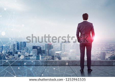 Rear view of businessman standing on skyscraper roof looking at city. Glowing network hologram in the foreground. Toned image double exposure