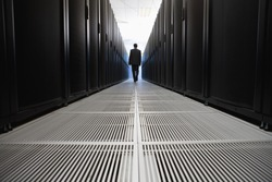 Rear view of businessman walking in server room in Cape Town, South Africa