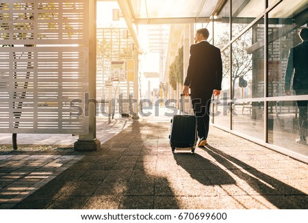 Rear view of businessman walking with bag outside airport. Young business traveler pulling suitcase on city street.