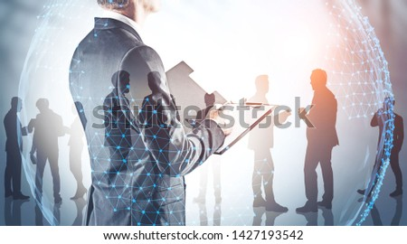 Rear view of businessman with clipboard with his teammates silhouettes and double exposure of planet hologram. Concept of international company and trade. Toned image
