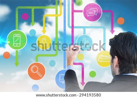 Rear view of businessman writing with a white chalk against blue sky #294193580