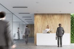 Rear view of businessmen near a white reception desk with two laptops standing on it in front of a wooden office wall. There are glass wall offices to the left.