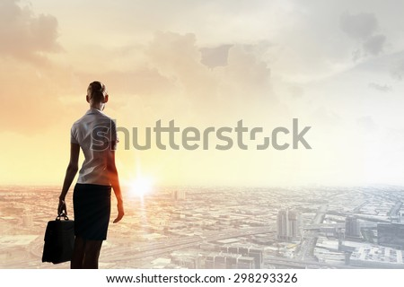 Rear view of businesswoman look at sunrise above city