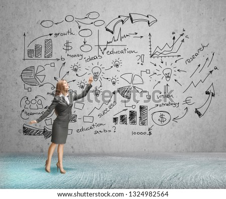 Rear view of businesswoman looking at infographs on wall #1324982564