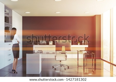 Rear view of businesswoman standing in black CEO office with white bookcases, computer table and shelf with folders. Concept of manager lifestyle. Toned image #1427181302