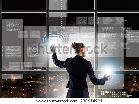 Rear view of businesswoman touching icon of media screen #230614921